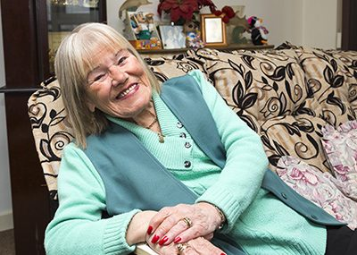 Woman in her 70s sitting on her sofa smiling.