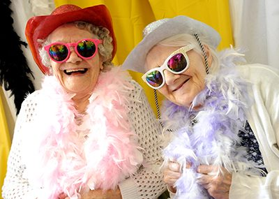Two older women wearing sunglasses and brightly coloured feather boas