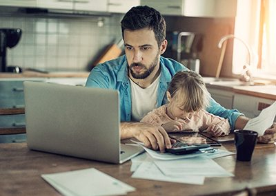 Photo of a father and daughter sitting in kitchen,father is doing home financials while daughter is having fun with digital tablet