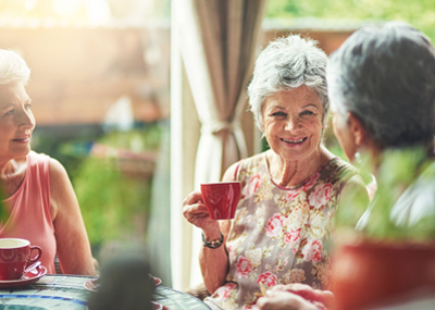 Three older women having tea in a conservatory.
